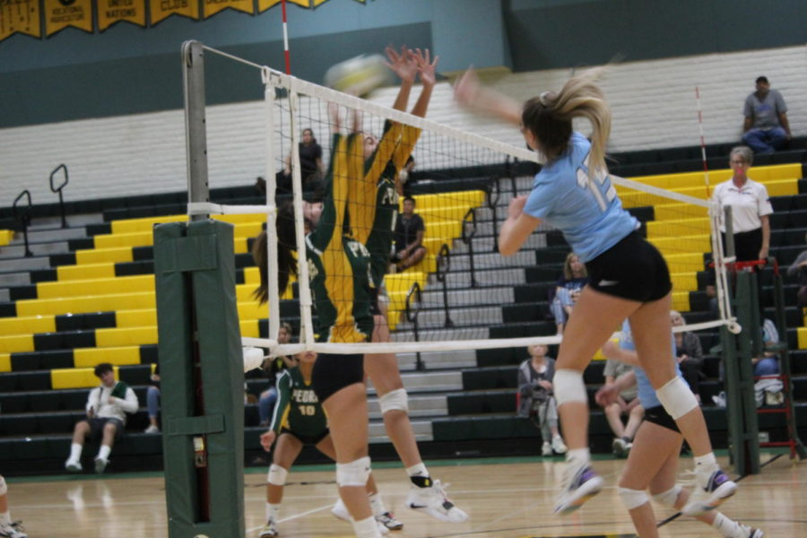 Bailey Fuches hitting outside, set by Emee Fellens.